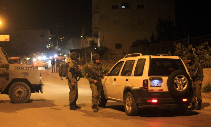 Israeli soldiers search a car in the village of Beit Anun, West Bank, April 2, 2015. (AP Photo/Mahmoud Illean)