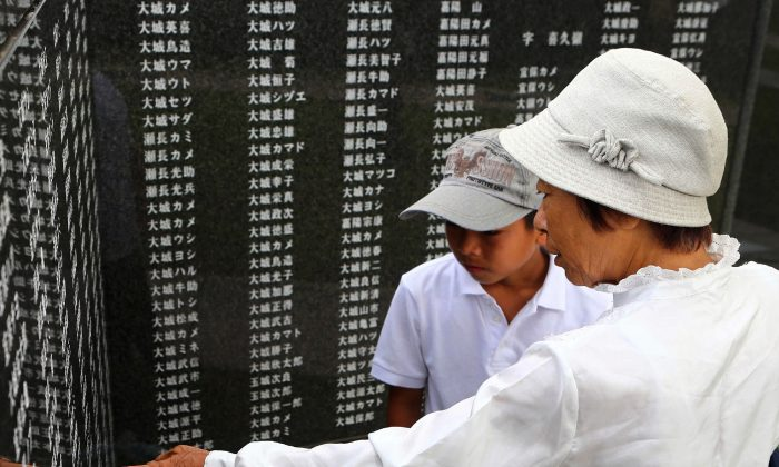 Relatives look at names on a Battle of Okinawa stone monument at Peace Memorial Park in Itoman on the island of Okinawa, Japan, on June 23, 2014. (JIJI PRESS/AFP/Getty Images)