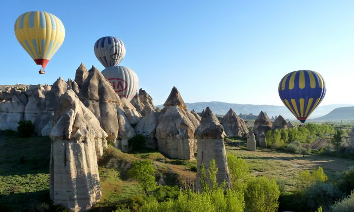 Hot air balloons glide over Cappadocia's fairy chimney wonderland. Sedimentary rocks, formed from volcanic material millions of years ago, were eroded by the elements into minaret and pillar shapes, which became known as fairly chimneys. (Manos Angelakis)