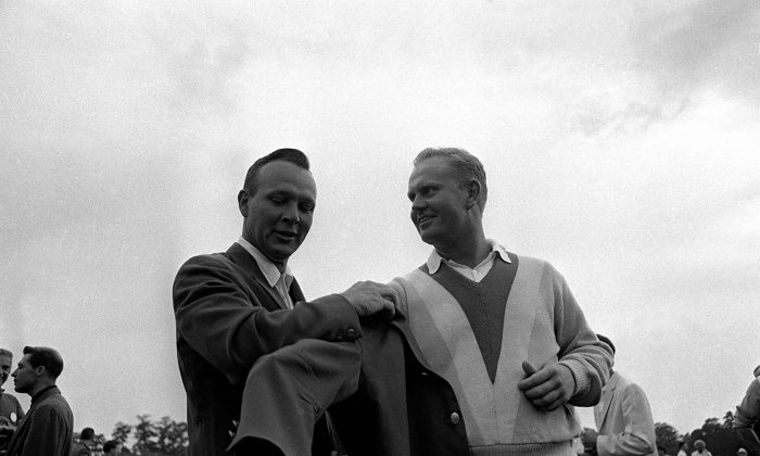 Arnold Palmer (L) helps Jack Nicklaus into the traditional green jacket after Nicklaus' nine-stroke victory at Augusta National Golf Club, April 11, 1965. (AP Photo)