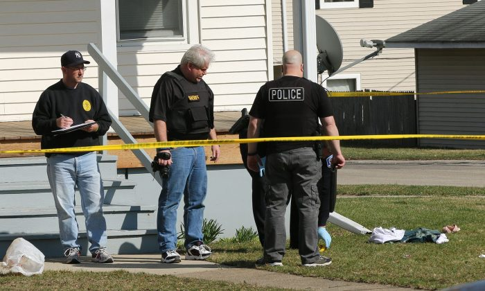 Investigators look over the scene following a police involved shooting in Zion, Ill. on Saturday, April 2, 2015, after a Zion Police officer was involved in a fatal shooting. (AP Photo/The Chicago Tribune, Joe Shuman)