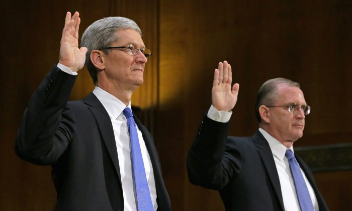 Apple CEO Timothy Cook (L) and Apple head of tax operations Phillip Bullock are sworn in before testifying to the Senate Homeland Security and Governmental Affairs Committee's Investigations Subcommittee about the company's offshore profit shifting and tax avoidance on Capitol Hill on May 21, 2013. (Chip Somodevilla/Getty Images)