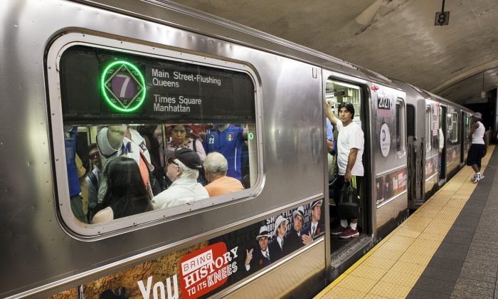 People wait on a 7 train that is being held at the Grand Central subway station on July 30, 2014.  (Samira Bouaou/Epoch Times)