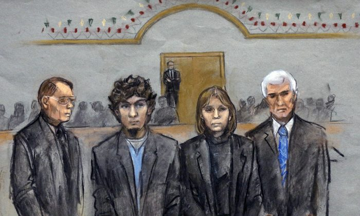 In this courtroom sketch, Dzhokhar Tsarnaev, second from left, is depicted standing with his defense attorneys as the jury presents its verdict in his federal death penalty trial Wednesday, April 8, 2015, in Boston. (AP Photo/Jane Flavell Collins)
