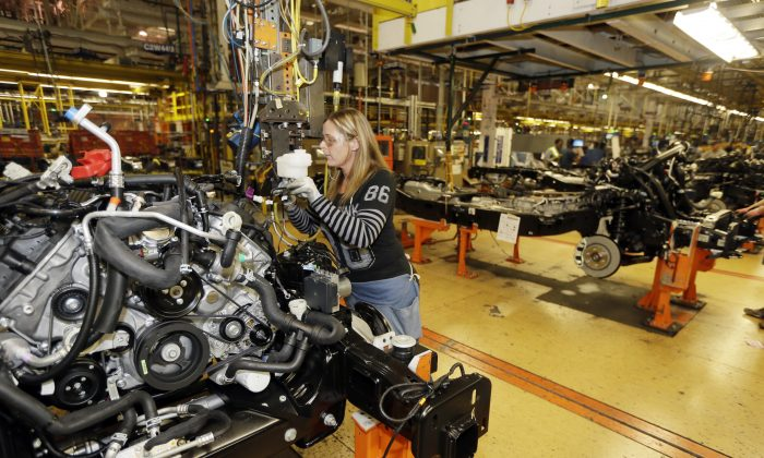 In a photo from Nov. 6, 2014, Jamie Winkles works on the brake line on the new Ford F-150 truck at the Rouge Truck Plant in Dearborn, Mich. (AP Photo/Carlos Osorio)