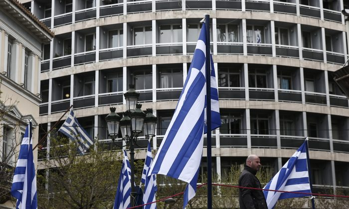 A municipal worker walks between Greek flags in Athens, on April 9, 2015.  (AP Photo/Yorgos Karahalis)
