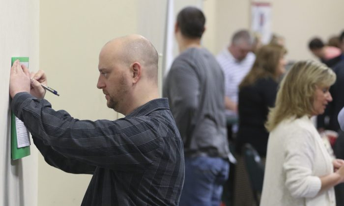In this April 2, 2015 photo, Daniel Marquardt from LaFayette, Ga., fills out an application during a huge 15-county job fair in Ringgold, Ga. The Labor Department released weekly jobless claims on Thursday, April 9, 2015. (AP Photo/Chattanooga Times Free Press, Dan Henry)