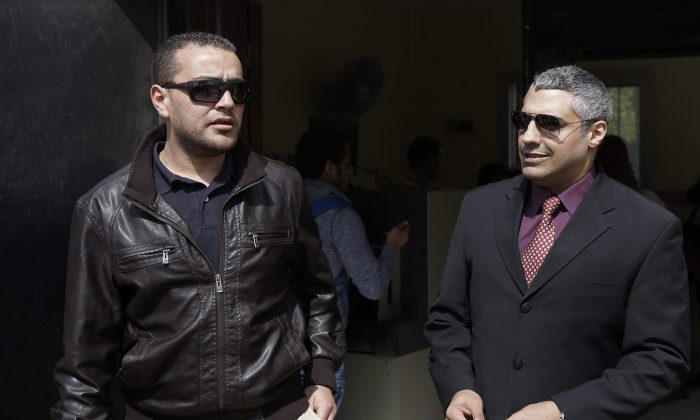 Al-Jazeera English journalists Canadian Mohamed Fahmy (R) and Egyptian Baher Mohammed leave court after a hearing in their retrial near Tora prison in Cairo on March 8, 2015. Fahmy's lawyer says the federal government is the only impediment to a new passport being issued for his client. (AP Photo/Hassan Ammar)