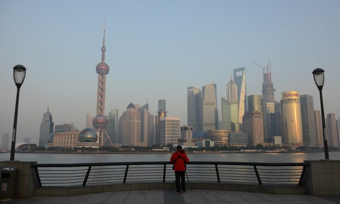 A photographer takes photos of the financial district of Pudong from the Bund in Shanghai on November 27, 2012.  (Peter Parks/AFP/Getty Images)