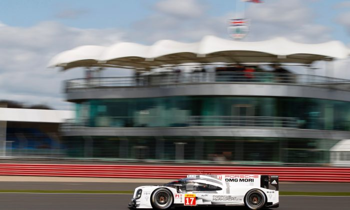 The #17 Porsche 919 Hybrid of Timo Bernhard, Brendon Hartley, and Mark Webber streaks past the buildings at Silverstone on its way to qualifying for the pole at the WEC Six Hours of Silverstone, April 11, 2015. (presse.porsche.de/)