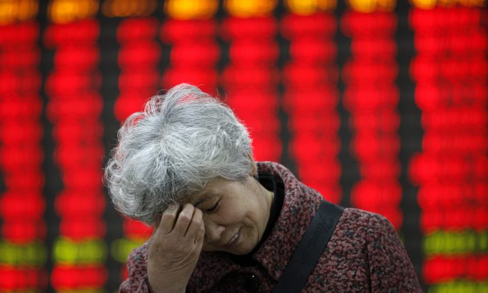An investors stands in front of a stock ticker board on April 7 in Huaibei, Anhui Province, China.(ChinaFotoPress / Stringer)