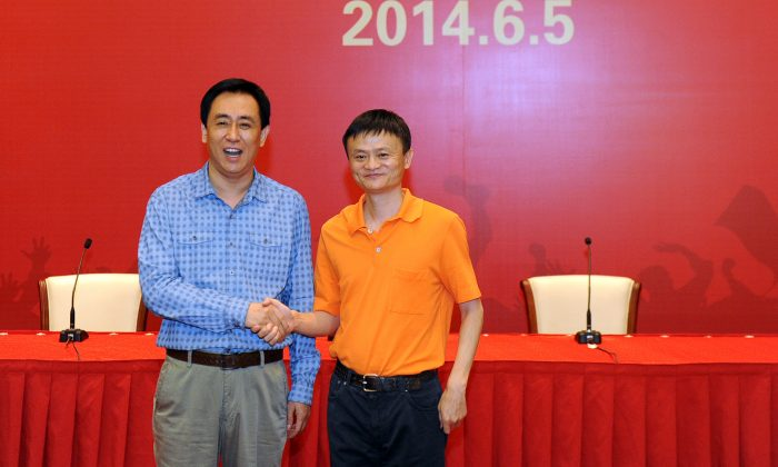 Founder and chairman of Alibaba Group Jack Ma (R) shakes hands with Chairman of Evergrande Group Xu Jiayin during a signing ceremony between Alibaba Group and Evergrande Group regarding Alibaba buying 50 percent of shares in Guangzhou Evergrande on June 5, 2014 in Guangzhou, Guangdong Province of China. (ChinaFotoPress/ChinaFotoPress via Getty Images)