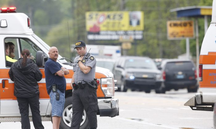 Authorities respond to a scene near a shooting Monday, April 13, 2015, in Jemison, Ala. A gunman entered a doctor's office in Jemison, shot a woman and fled to a nearby home, police said. (AP Photo/Brynn Anderson)