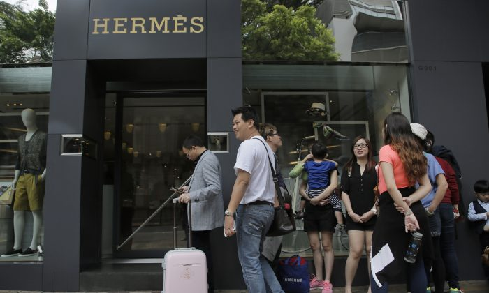 Mainland Chinese tourists queue up outside a luxury brand boutique at a shopping district in Hong Kong, April 12, 2015. (AP Photo/Vincent Yu)