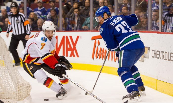 Henrik Sedin of the Vancouver Canucks plays the puck off the back of the net to elude the check of T.J. Brodie of the Calgary Flames on Jan. 10, 2015 at Rogers Arena in Vancouver. The two Canadian division rivals are slated for an interesting battle in the first round of the NHL Playoffs. (Rich Lam/Getty Images)
