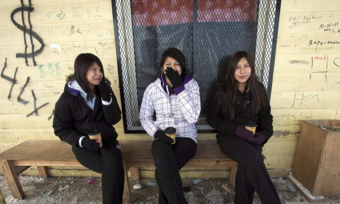 Teenage girls enjoy a coffee outside the local store on the Fort Hope First Nation in Ontario. Many of Canada's First Nations communities have long grappled with poverty. The Live Below the Line challenge raises money for organizations that deliver programs focused on nutrition, water, health and sanitation, and education. (The Canadian Press/Ryan Remiorz)