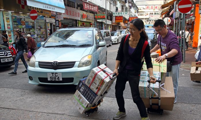 Two mainlanders carry their goods on trolleys walking across street at Sheung Shui, Northern District of Hong Kong on April 12, 2015. (Epoch Times)