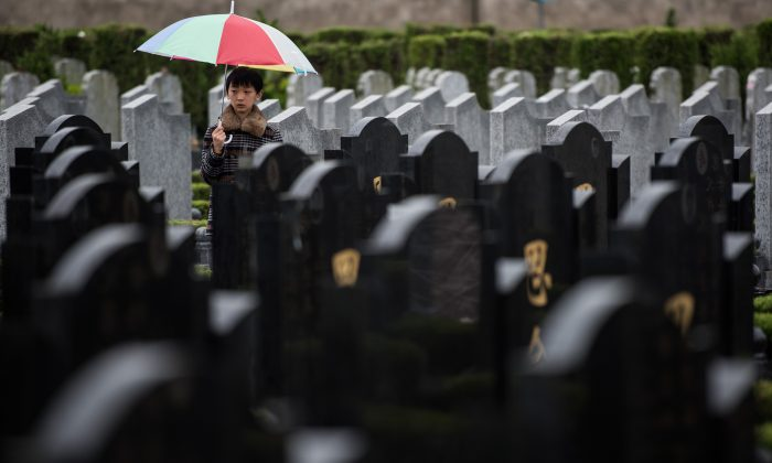 "A boy stands between graves during the annual ""Qingming"" festival, or Tomb Sweeping Day, at a public cemetery in Shanghai on April 6, 2015. (Johannes Eisele/AFP/Getty Images)"
