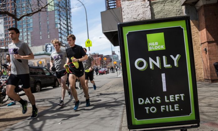 A group of men run past an H&R Block on April 15, 2015 in New York City. Today is the deadline for filing federal income taxes.  (Andrew Burton/Getty Images)