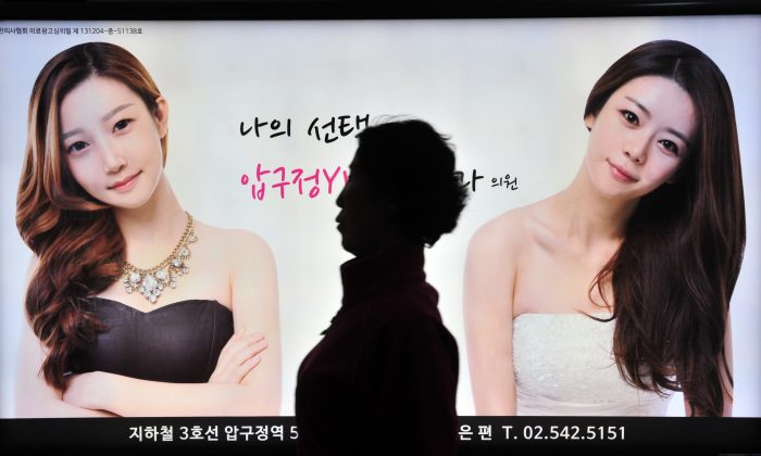 A pedestrian walks past an advertisement for plastic surgery clinic at a subway station in Seoul on March 26, 2014.  (Jung Yeon-Je/AFP/Getty Images)