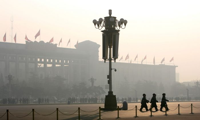 Chinese police officers patrol Tiananmen Square while security cameras monitor the area in Beijing in this file photo. (Cancan Chu/Getty Images)