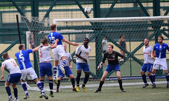 Wanderers' Andrew Wylde (blue 15) has his header cleared off of the line during their 1-all draw with Squadron (white) in their Yau Yee League Division 1 match at Sports Road on Sunday April 12, 2015. (Bill Cox/Epoch Times)