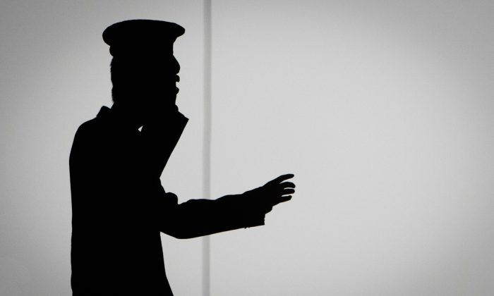 A Chinese security guard talks on his cell phone in Beijing on Oct. 10, 2014. (FRED DUFOUR/AFP/Getty Images)