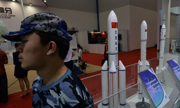 A security guard stands next to models of Chinese rockets on display Beijing on September 24, 2013. The Chinese regime is testing weapons that could soon endanger satellites in all orbits. (Mark Ralston/AFP/Getty Images)