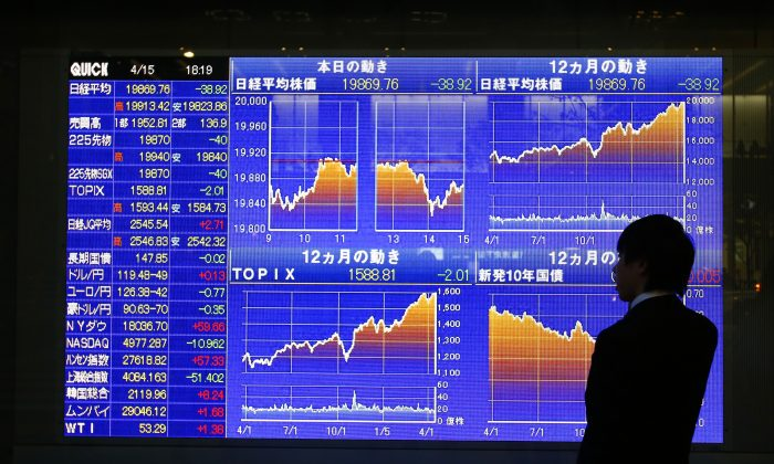 A man looks at an electronic stock indicator of a securities firm in Tokyo, Japan, on April 15, 2015. Japan surpassed China as the top foreign holder of U.S. debt for the first time since the 2008 financial crisis. (AP Photo/Shizuo Kambayashi)
