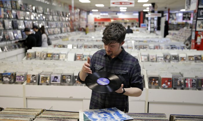 Record clerk Josh Kelly wipes a dust speck from a used LP record as he put it in a sales bin at Vintage Vinyl Records Tuesday, in Fords, N.J., on April 14, 2015. (AP Photo/Mel Evans)