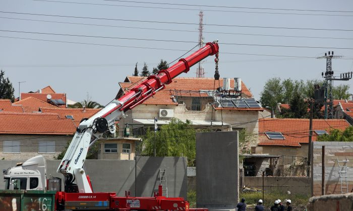 An Israeli crane lifts a section of concrete as they build a defensive wall around the Israeli settlement of Beit El, in the occupied West Bank north of Ramallah on April 7, 2015, next to a road used by Palestinians from the adjacent Jalazon refugee camp. (Abbas Momani/AFP/Getty Images)