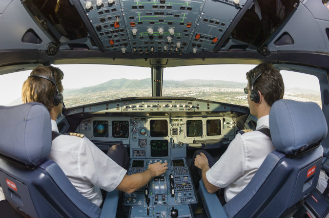 Pilots in an airplane cockpit via Shutterstock*