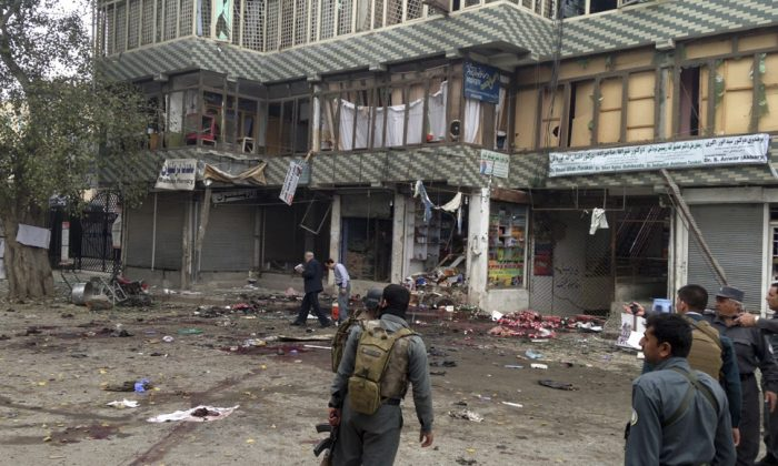 Afghan security forces inspect the site of a suicide attack near a bank branch in Jalalabad, east of Kabul, Afghanistan, Saturday, April 18, 2015. (AP Photo)