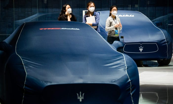Women stand next to Maserati cars ahead of the 16th Shanghai International Automobile Industry Exhibition in Shanghai on April 19, 2015. (JOHANNES EISELE/AFP/Getty Images)