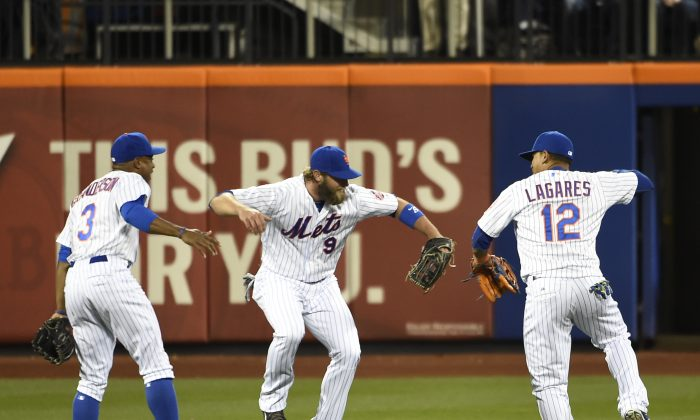 New York Mets right fielder Curtis Granderson (3), left fielder Kirk Nieuwenhuis (9) and center fielder Juan Lagares (12) celebrate their 5-4 win over the Miami Marlins in a baseball game at Citi Field on April 18, 2015, in New York. (AP Photo/Kathy Kmonicek)