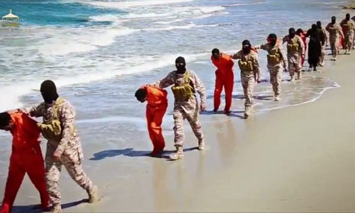 This undated image made from a video released by Islamic State militants, Sunday, April 19, 2015, appears to show the killing of a group of captured Ethiopian Christians in Libya. The 29-minute video released online Sunday purportedly shows two groups of captives. It says one group is held by an IS affiliate in eastern Libya and the other by an affiliate in the south. A masked fighter delivers a long statement before the video switches between footage that purportedly shows the captives in the south being shot dead and the captives in the east being beheaded on a beach. (Militant video via AP)