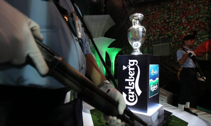 Security guards in Malaysia are posted next to the UEFA Euro 2012 trophy on display at a shopping mall in Bandar Sunway on April 6, 2012. Officials in Malaysia say that triads are infiltrating the country's security companies. (MOHD RASFAN/AFP/Getty Images)