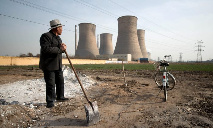 A man looks towards chimney stacks in a field outside a power plant in Xingtai, Hebei province, on March 10, 2013. (Ed Jones/AFP/Getty Images)