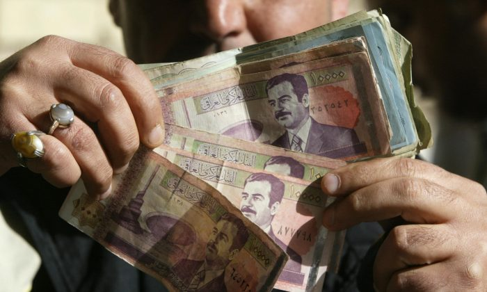 A street money exchange trader displays Iraqi dinar notes with the face of ousted dictator Saddam Hussein in Baghdad 13 January 2004, two days before the old bills will no longer be legal tender. (Ramzi Haidar/AFP/Getty Images)