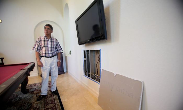 Alfonso Sanchez poses for photos in the game room of his Davie, Fla. home Thursday, Oct. 15, 2009. (AP Photo/J Pat Carter)