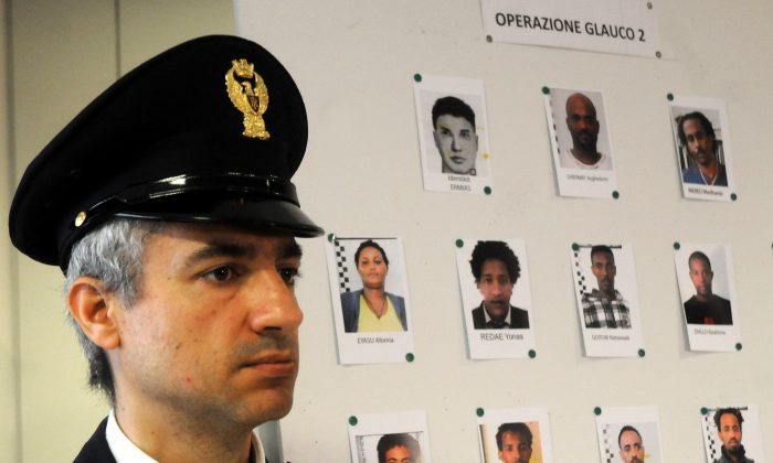 An Italian Police officer stands next to mug shots of alleged migrant traffickers shown during a press conference, in Palermo, Sicily, Italy, Monday, April 20, 2015.(AP Photo/Alessandro Fucarini)