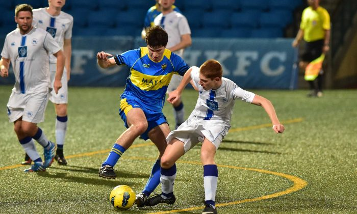 Colts (white kit) and Boca Seniors (blue kit) vie for the ball during Colts 4-nil win in the Yau Yee League, Division 1 match at Sports Road on Sunday April 19, 2015. (Bill Cox/Epoch Times)
