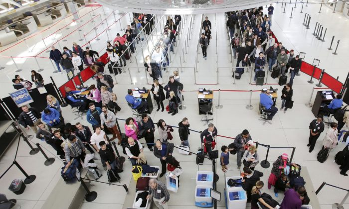 In this Oct. 30, 2014 photo, passengers line up to pass through security before boarding flights at John F. Kennedy International Airport in New York. (AP Photo/Mark Lennihan)