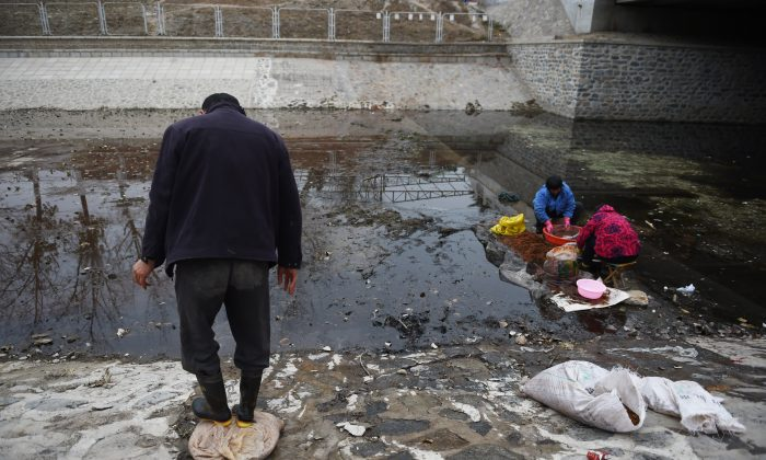 Chinese women washing seeds on Nov. 27, 2014 in a disused Beijing canal. (GREG BAKER/AFP/Getty Images)