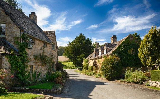 Ancient cotswold stone houses and flower garden in Cotswolds via Shutterstock*