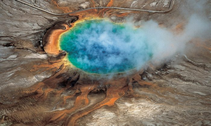 "The gorgeous colors of Yellowstone National Park's Grand Prismatic hot spring are among the park's myriad hydrothermal features created by the fact that Yellowstone is a supervolcano – the largest type of volcano on Earth. A new University of Utah study reports discovery of a huge magma reservoir beneath Yellowstone's previously known magma chamber. That doesn't increase the risk of an eruption, but means scientists are getting a better view of Yellowstone's volcanic plumbing system. (""Windows into the Earth,"" Robert B. Smith and Lee J. Siegel)"