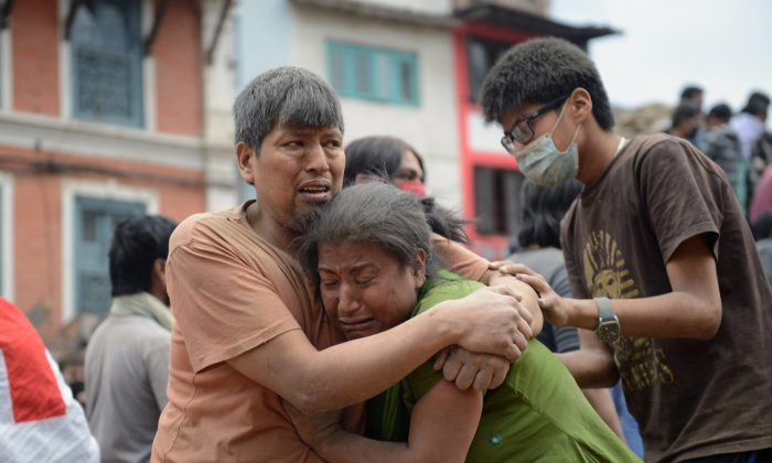 A Nepalese man and woman hold each other in Kathmandu on April 25, 2015 after the devastating 7.8 magnitude earthquake.(Prakash Mathema/AFP/Getty Images)