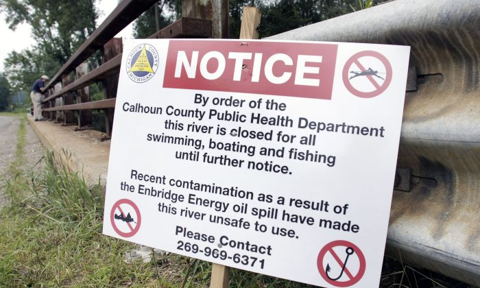 A sign is posted on a bridge to indicate water contamination after an oil spill of approximately 800,000 gallons of crude in the Kalamazoo River on July 28, 2010 in Marshall, Mich. (Bill Pugliano/Getty Images)