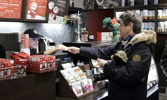 In this Dec. 6, 2010 file photo, a customer pays for a coffee beverage at Starbucks in the SoHo neighborhood of New York. (AP Photo/Mark Lennihan)