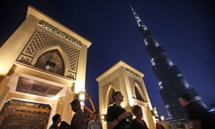 With the world tallest tower, Burj Khalifa, in background, tourists and visitors cross a bridge to Souk Al Bahar in Dubai, United Arab Emirates, Monday, April 13, 2015. (AP Photo/Kamran Jebreili)